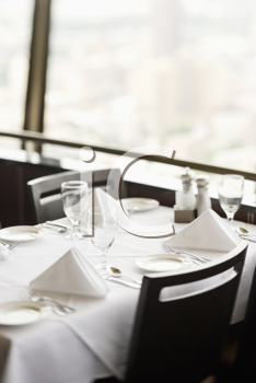High angle view of a restaurant table with place settings and a white tablecloth.  The table is by a window. Vertical shot.