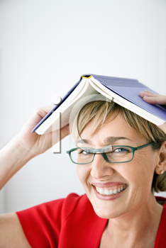 Woman smiling holding book on head.