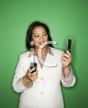 Portrait of pretty African American businesswoman holding cellphone in each hand.