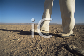 Royalty Free Photo of a Man's Legs Walking in a Desert