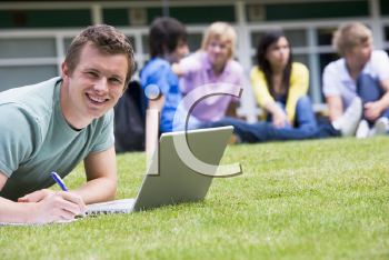 Royalty Free Photo of a Student Taking Notes From a Laptop With Other People in the Background