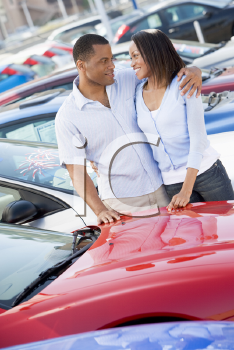 Royalty Free Photo of a Couple Looking at Each Other While Shopping for Cars