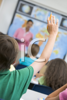 Royalty Free Photo of a Teacher and Class With a Child Raising His Hand