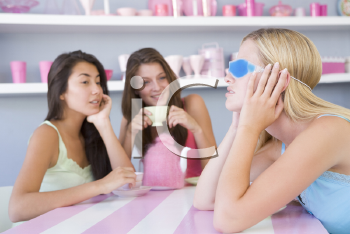 Royalty Free Photo of a Young Woman With a Hangover Sitting at a Table With Friends