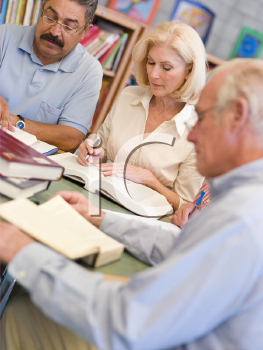 Royalty Free Photo of Three People at a Library Table
