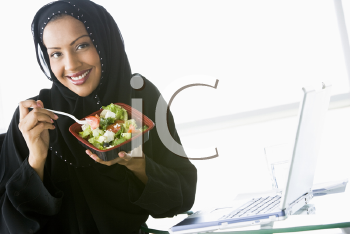 Royalty Free Photo of a Woman Wearing a Headset Eating a Salad at a Laptop
