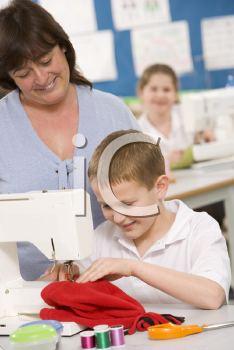 Royalty Free Photo of a Boy Sewing With His Teacher Behind Him