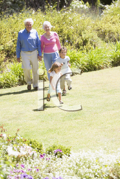 Royalty Free Photo of Grandparents in the Garden With Their Grandchildren