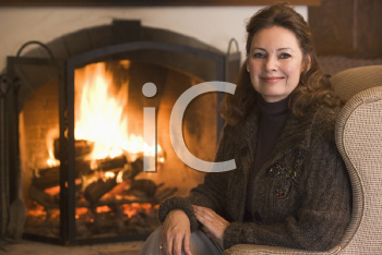 Royalty Free Photo of a Woman By a Fireplace