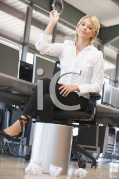 Royalty Free Photo of a Woman Throwing Paper in the Trash Can