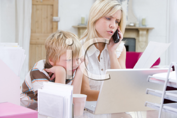 Royalty Free Photo of a Woman on the Phone With Her Son Looking at a Laptop