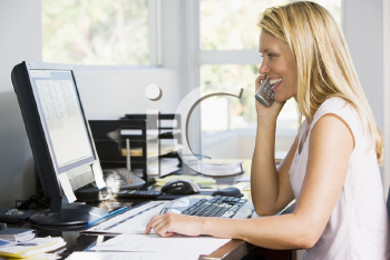 Royalty Free Photo of a Woman at a Home Office Talking on the Phone