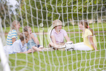 Royalty Free Photo of Kids on a Field Behind a Soccer Net