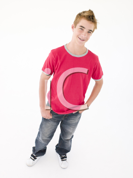 Teenage boy with hands in pockets smiling