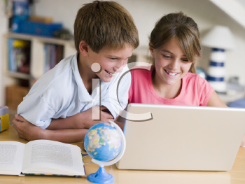 Royalty Free Photo of a Boy and Girl Doing Homework on a Laptop