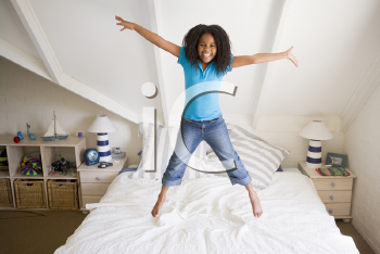 Royalty Free Photo of a Girl Jumping on Her Bed
