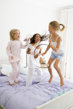 Royalty Free Photo of Three Girls Jumping on a Bed