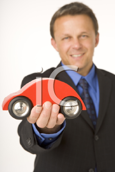 Royalty Free Photo of a Businessman Holding a Toy Car