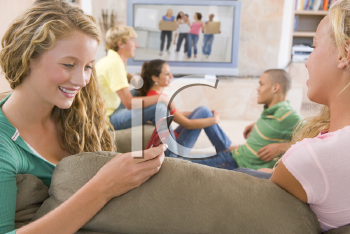 Royalty Free Photo of Teens Watching TV and a Girl on a Cellphone