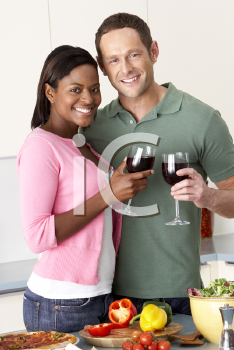 Royalty Free Photo of a Couple Enjoying Wine While Preparing a Meal