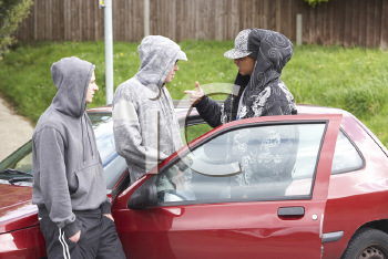 Royalty Free Photo of a Group of Young Men at a Car