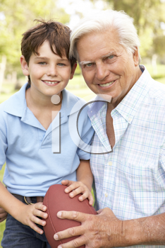 Royalty Free Photo of a Man and His Grandson With a Football