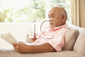 Royalty Free Photo of a Man Reading a Book and Drinking Coffee