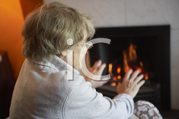 Royalty Free Photo of a Woman Warming Her Hands at a Fire