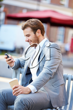 Businessman On Park Bench With Coffee Using Mobile Phone