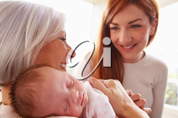 Mother And Grandmother With Sleeping Newborn Baby Daughter