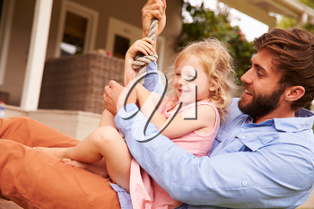 Father playing with daughter on a rope swing in a garden