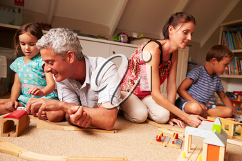 Parents playing with kids and toys in an attic playroom