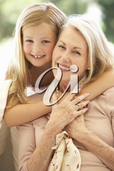 Grandmother With Granddaughter Laughing Together On Sofa