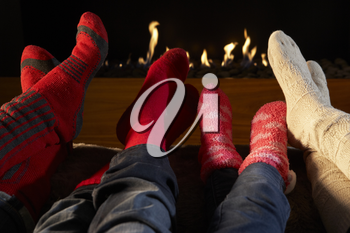Four pairs feet in socks warming by fire