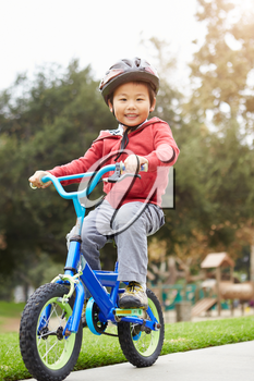 Young Boy Riding Bike In Park