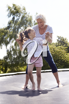 Grandmother And Granddaughter Bouncing On Trampoline
