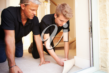Two men laying underlay for flooring in a house