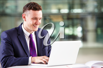 Young Caucasian businessman using laptop computer at work