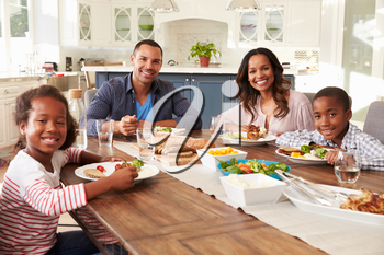 Parents and children eating at kitchen table look to camera