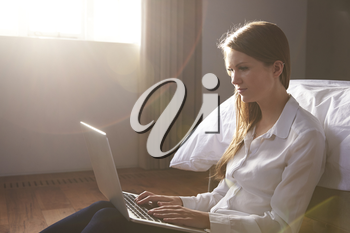 Woman Sitting On Bed In Bedroom Using Laptop Computer