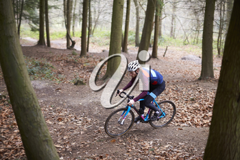 Young man cross-country cycling between trees in a forest
