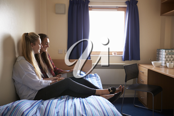 Female Students Working In Bedroom Of Campus Accommodation