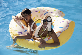 Children Having Fun With Inflatable In Outdoor Swimming Pool