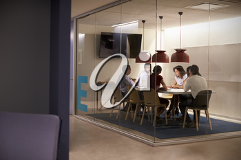 Corporate business team at table in a meeting room cubicle