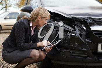 Loss Adjuster With Digital Tablet Inspecting Damaged Car
