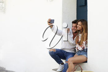 Happy couple sitting on stairs taking a selfie, Ibiza, Spain