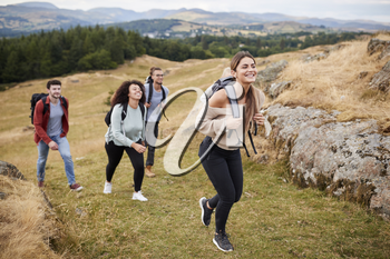 Multi ethnic group of five young adult friends hiking across a field uphill towards the summit, close up