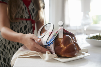 Girl covering challah bread for Shabbat meal, close up