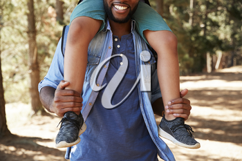 Close Up Of Father Walking In Woods Carrying Son On Shoulders