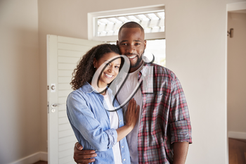 Portrait Of Couple By Open Front Door In Lounge Of New Home
